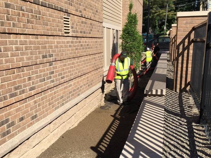 Worker spraying mulch behind building